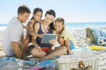 Familia usando tableta digital en la playa LANG_EVOIMAGES