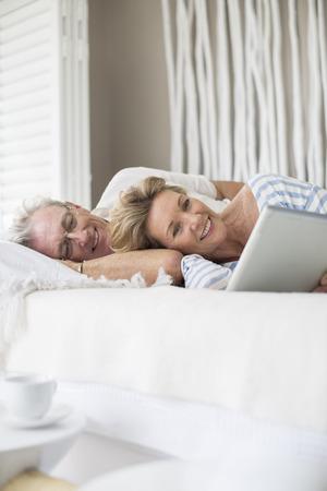 silver surfer: Older couple using digital tablet on bed LANG_EVOIMAGES