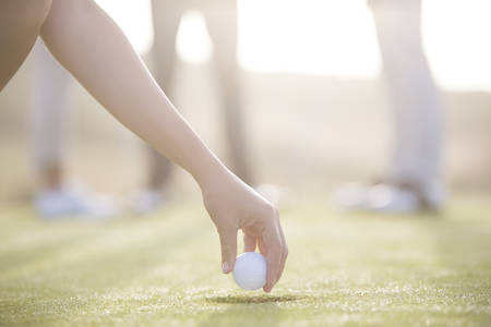 Woman teeing golf ball on course