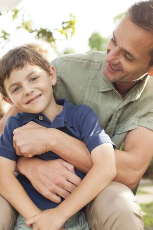 smile close up: Father and son hugging outdoors