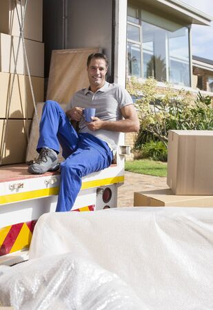 leaning on the truck: Mover enjoying cup of coffee in back of moving van LANG_EVOIMAGES