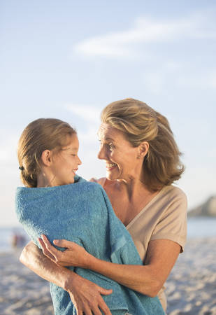 Older woman holding granddaughter on beach LANG_EVOIMAGES