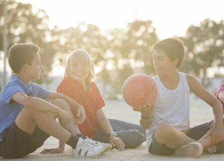 Children sitting with soccer ball outdoors LANG_EVOIMAGES