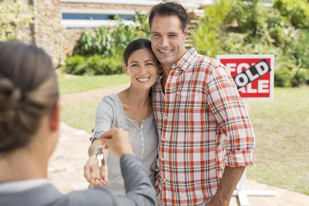 brazilian ethnicity: Realtor giving couple keys to new house