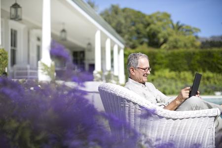silver surfer: Senior man using digital tablet in garden