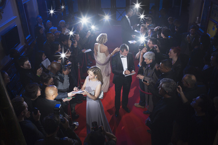 Well dressed celebrities signing autographs on red carpet LANG_EVOIMAGES