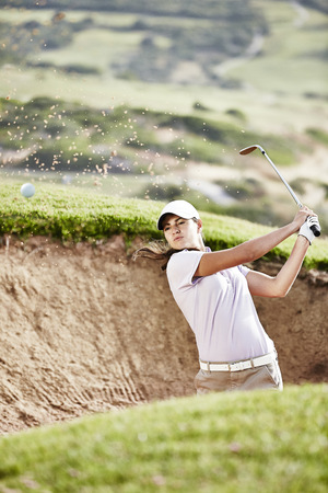 overcoming adversity: Woman swinging from sand trap on golf course LANG_EVOIMAGES