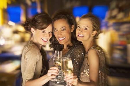 brazilian ethnicity: Smiling women toasting champagne glasses in nightclub LANG_EVOIMAGES