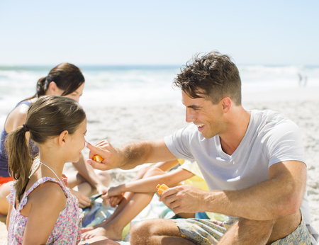 Father rubbing sunscreen on daughters nose at beach