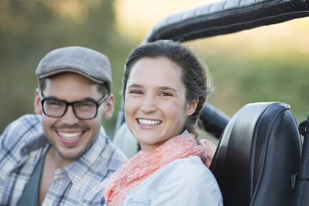 the jeep: Portrait of smiling couple in sport utility vehicle