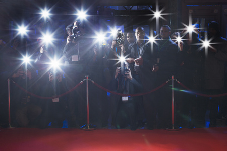 Paparazzi using flash photography behind rope on red carpet LANG_EVOIMAGES