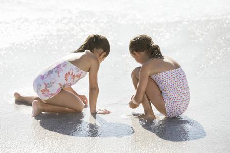 arrodillarse: Niñas jugando juntos en el surf en la playa