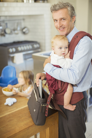 family: Businessman carrying baby in kitchen LANG_EVOIMAGES