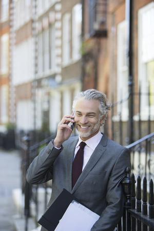 Businessman talking on cell phone on urban sidewalk
