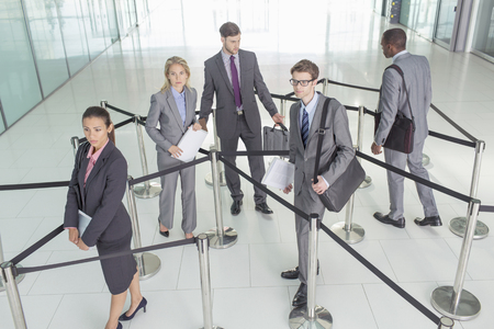 Business people standing in roped-off area LANG_EVOIMAGES