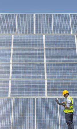 carbon neutral: Worker examining solar panels