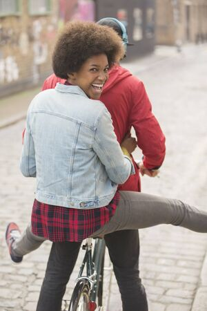 alternative living: Couple riding bicycle together on city street