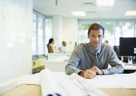 architect: Businessman reading blueprints in office