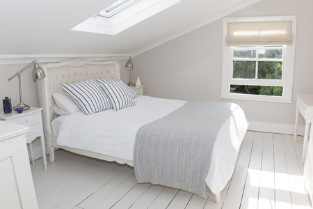 attic: Bed in whitewashed attic bedroom LANG_EVOIMAGES