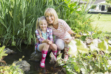 Grandmother and granddaughter smiling by pond LANG_EVOIMAGES