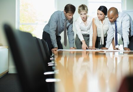 architect: Business people examining blueprints in meeting