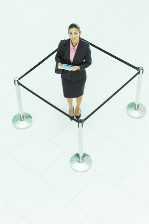 roped: Businesswoman standing in roped-off square