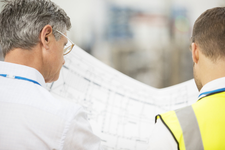architect: Workers reading blueprints in warehouse