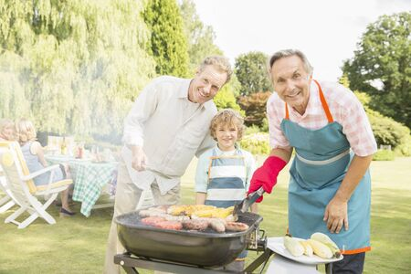 grill tongs sausage: Multi-generation men grilling meat and corn at barbecue in backyard