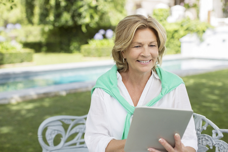 electronic book: Senior woman using digital tablet in backyard