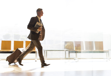 Businessman running with suitcase in airport corridor