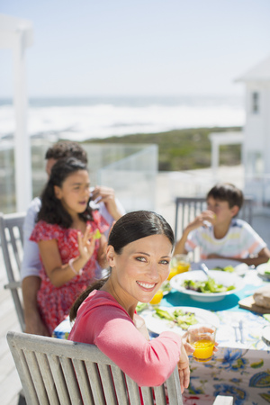 turn table: Family eating lunch at table on sunny patio overlooking ocean