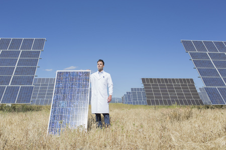 Scientist holding solar panel in rural landscape LANG_EVOIMAGES