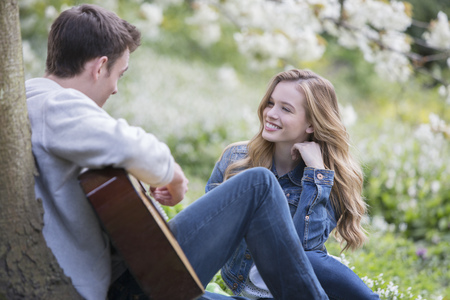 Man playing guitar for girlfriend outdoors