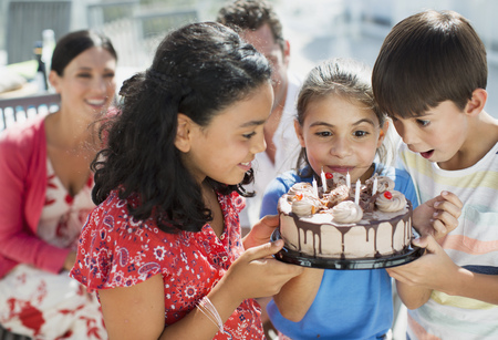 Children holding birthday cake outdoors