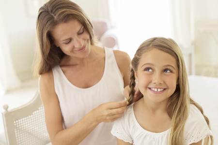 Mother braiding daughters hair