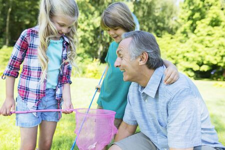 Man and grandchildren playing outdoors