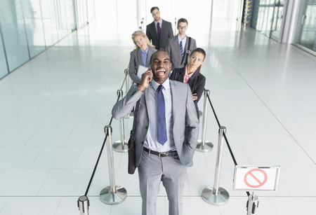 roped: Businessman talking on cell phone in line