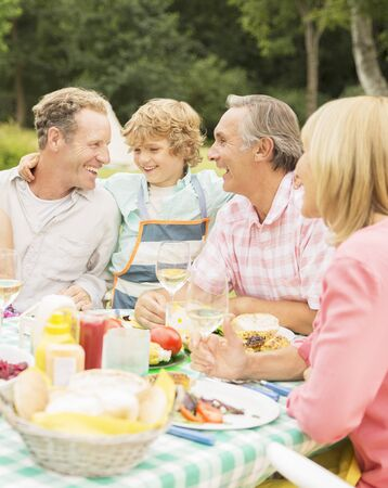 family: Family enjoying lunch at table in backyard