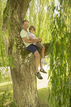 looking away from camera: Father and son sitting in tree