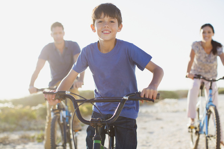 Family riding bicycles on sunny beach LANG_EVOIMAGES