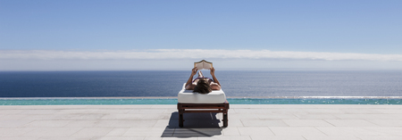 Woman relaxing on lounge chair at poolside overlooking ocean