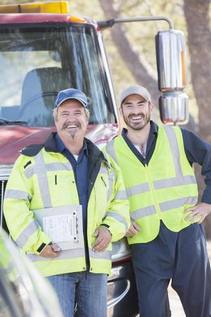 leaning on the truck: Portrait of confident roadside mechanics