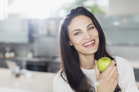 Portrait of smiling woman eating apple in kitchen