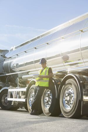truck driver: Worker with clipboard leaning on stainless steel milk tanker