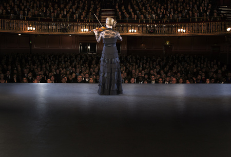 focus on foreground: Violinist performing on stage in theater LANG_EVOIMAGES