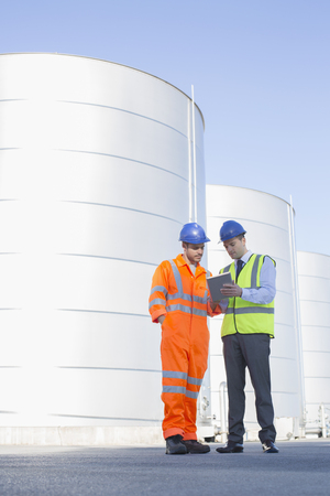 Businessman and worker using digital tablet next to silage storage towers