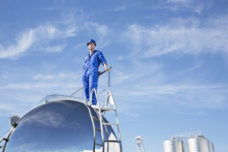 leaning on the truck: Worker standing on stainless steel milk tanker LANG_EVOIMAGES