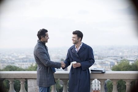 personas saludandose: Businessmen shaking hands at railing overlooking Paris, France