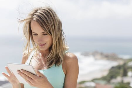 focus on foreground: Woman using digital tablet with ocean in background