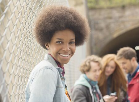 Woman smiling by chain link fence with friends in background
